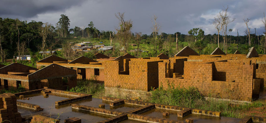 Unfinished housing that the mining company funded by a World Bank project in Liberia had promised to the people it displaced.